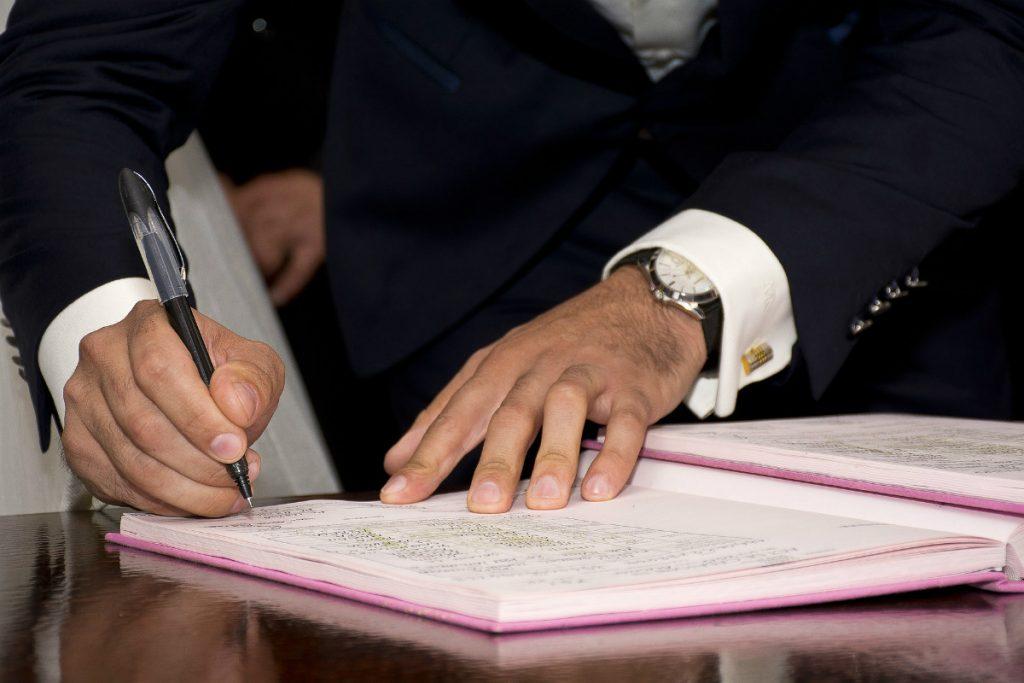 man zet een handtekening onder een document